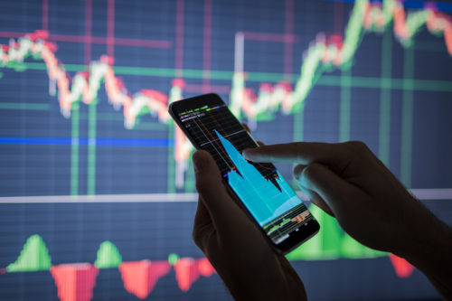 male-checking-stock-options-on-mobile-phone