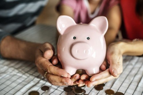 A cropped photo of a family holding a pink piggy bank with coins scattered around their hands.