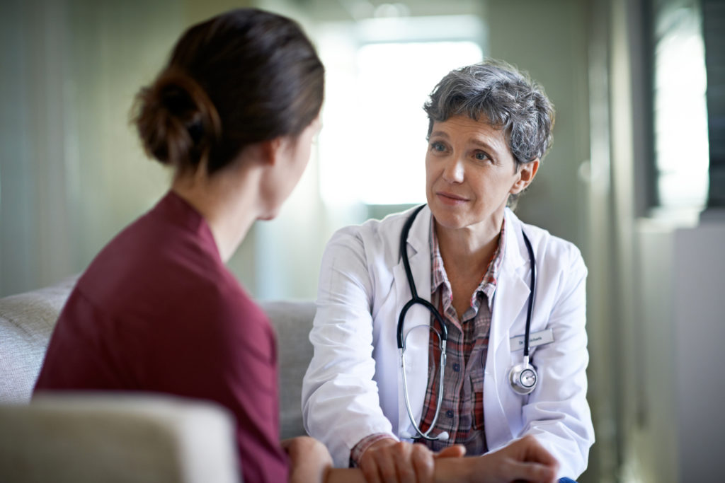 female doctor listens to female patient