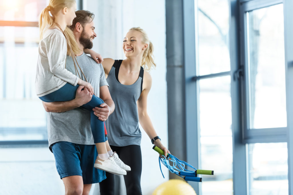 busy mom with happy family at gym