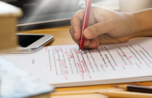 hand-using-red-pen-to-correct-grammar-mistakes