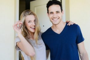 young-couple-hold-keys-to-new-house