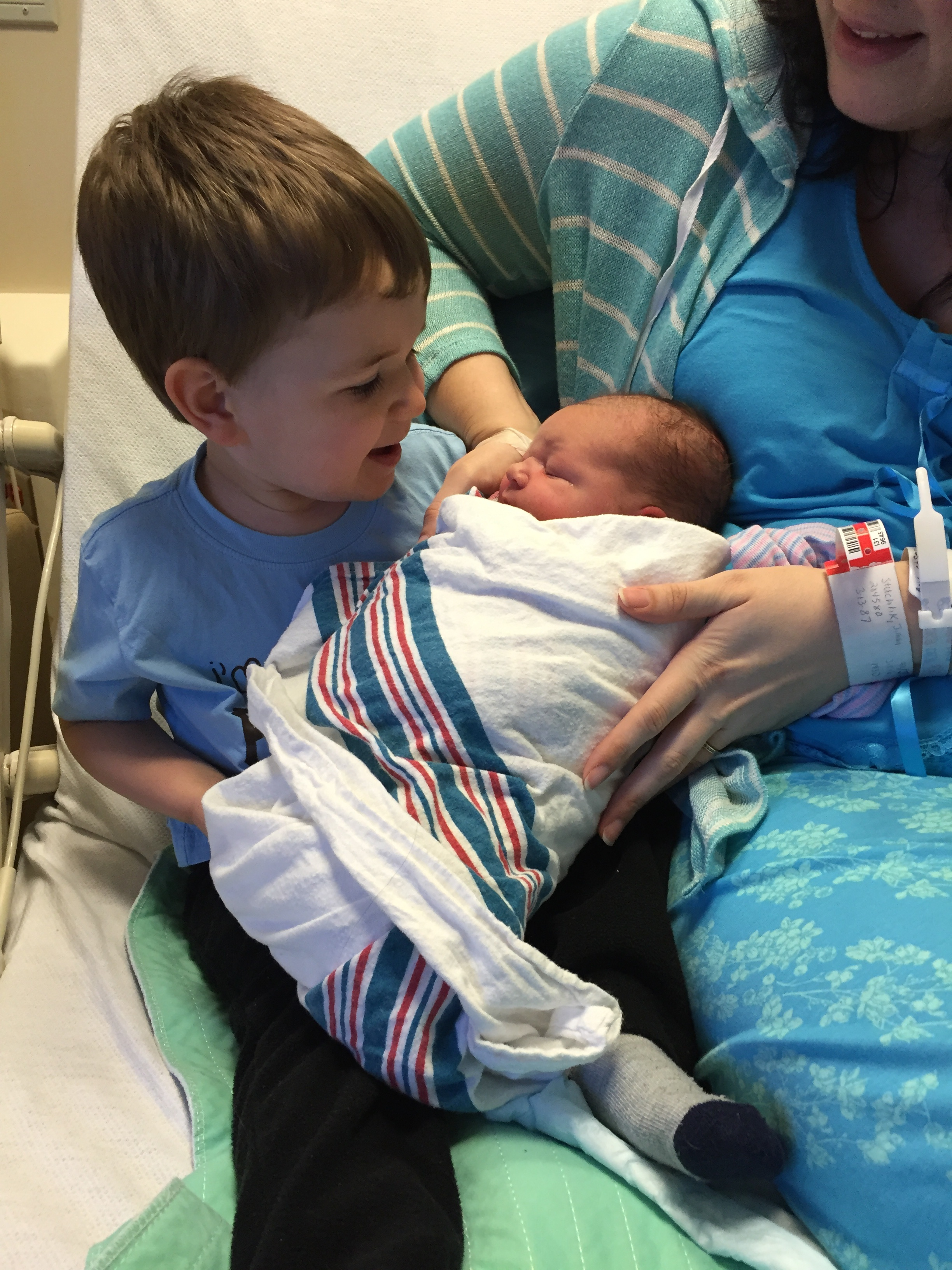 little-boy-welcoming-his-newborn-brother-with-mother-into-family