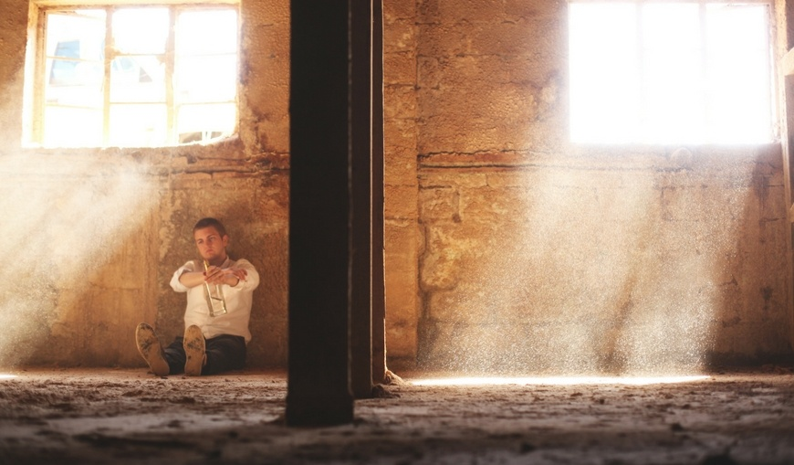 Man-sitting-in-abandoned-cellar-drinking-bottle-of-alcohol