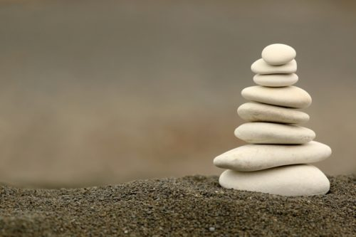 Several smooth, white stones stacked on top of one another in decreasing size from bottom to top.