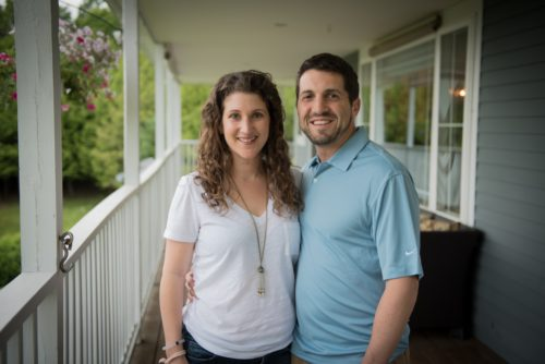 man-and-woman-stand-on-porch-embracing