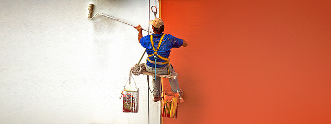 man painting a wall orange and white