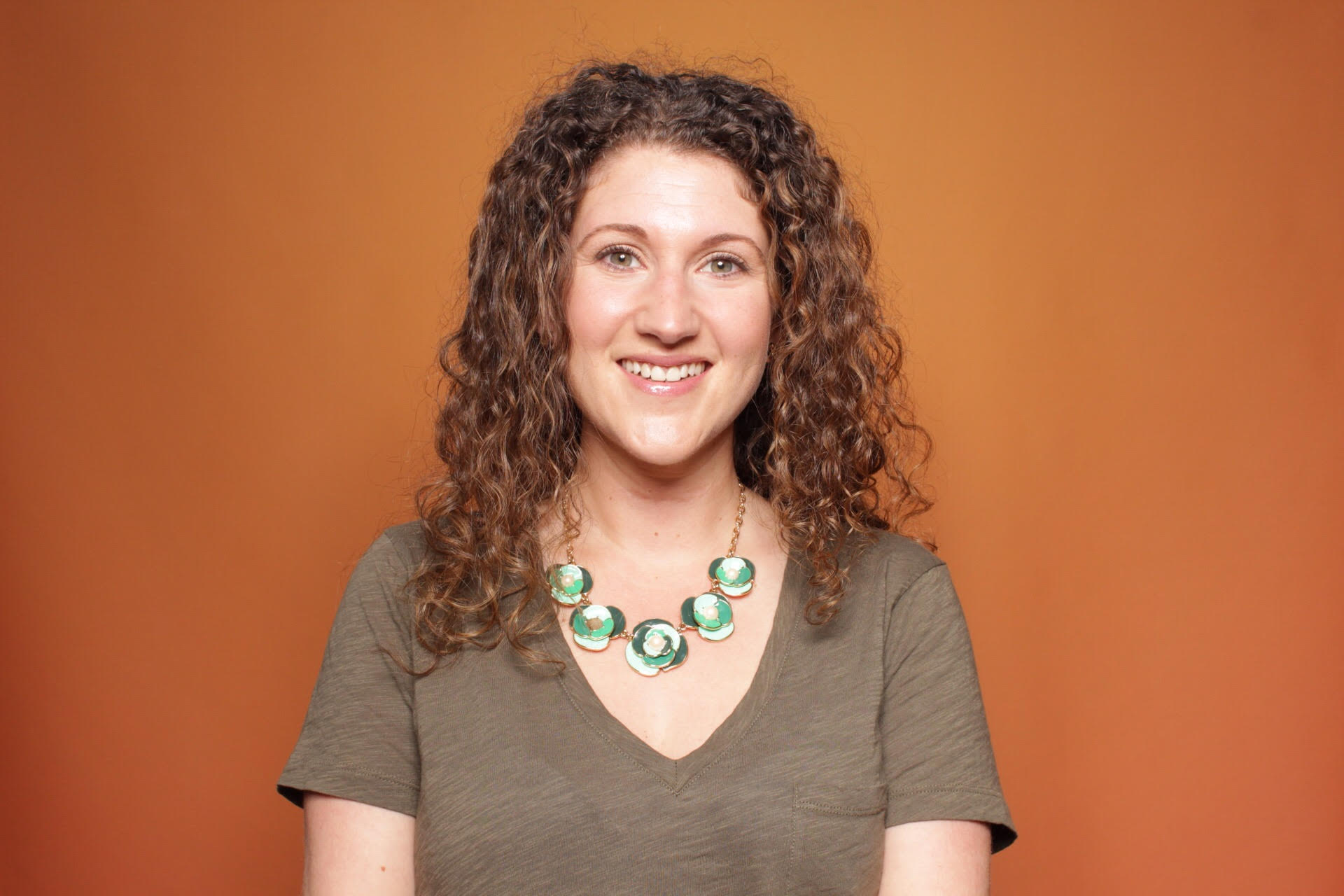 woman-with-curly-brown-hair-green-statement-necklace-smiling