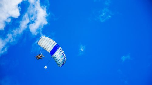A skydiver floats toward the ground with an opened parachute against a blue sky