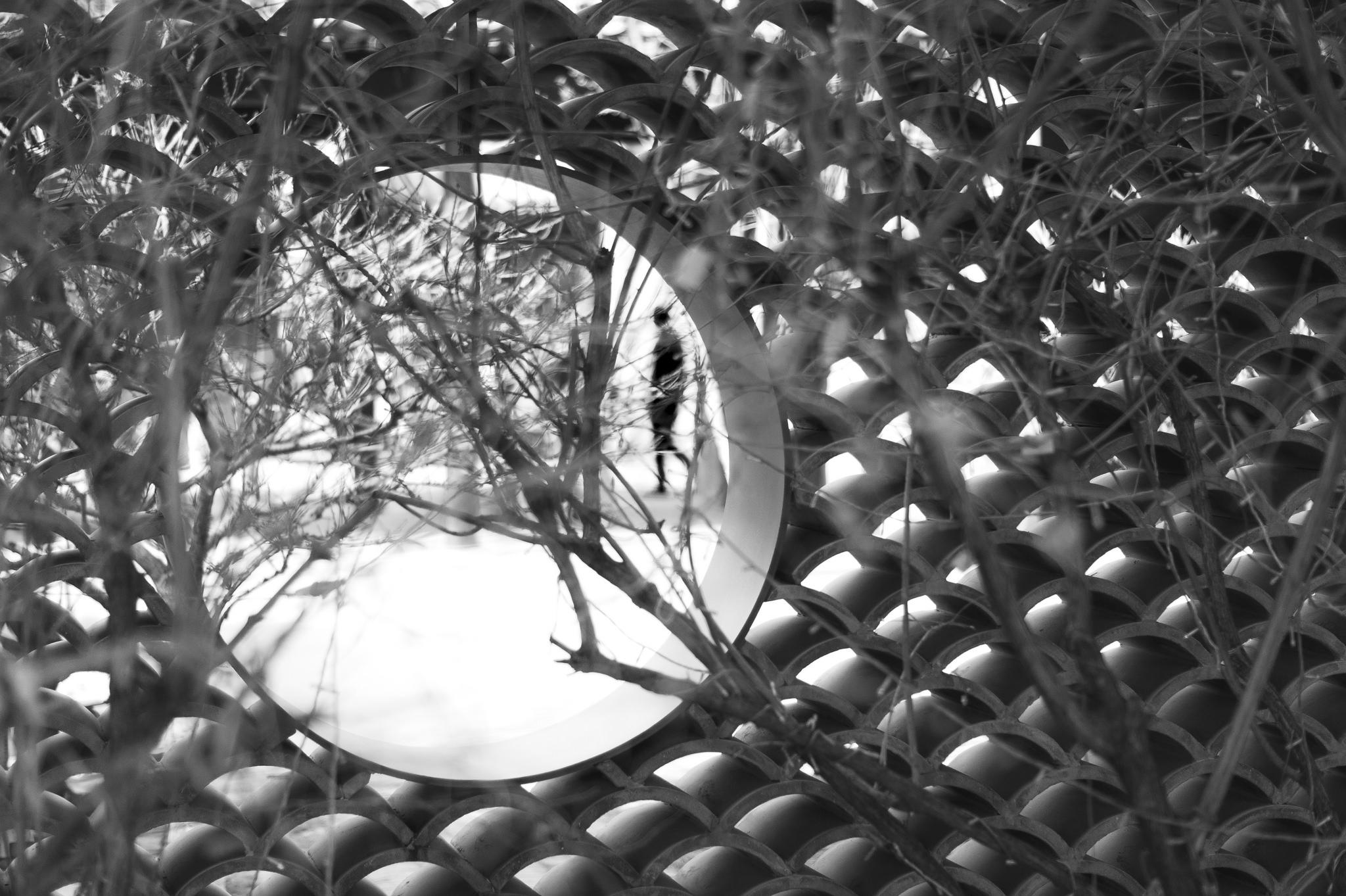 fence-with-peephole-focused-on-blurry-man