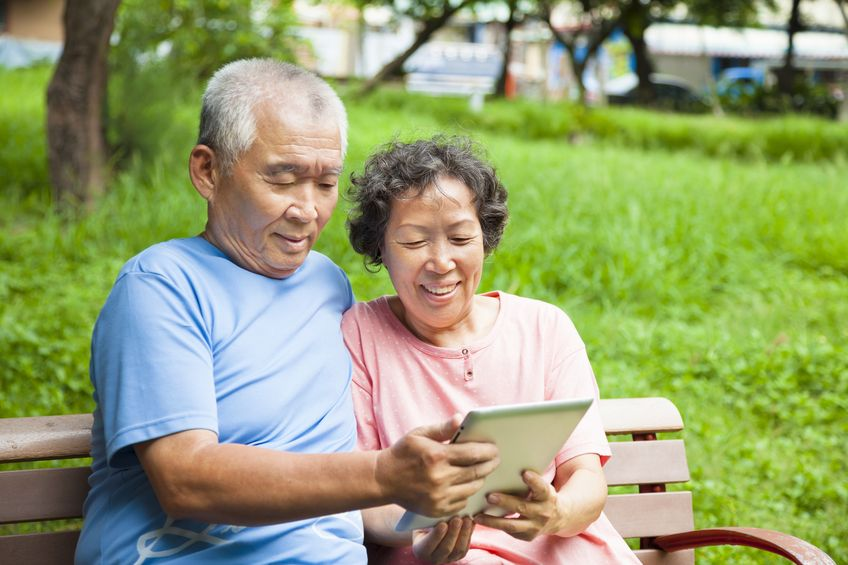 baby-boomer-couple-sit-on-bench-looking-at-ipad