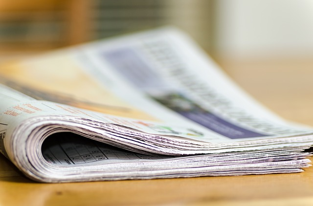 selective focus photography of a folded newspaper on a wooden table