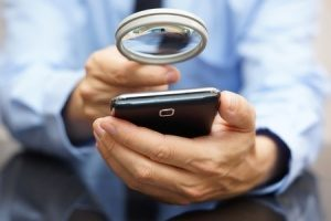 man-holds-magnifying-glass-up-to-smartphone