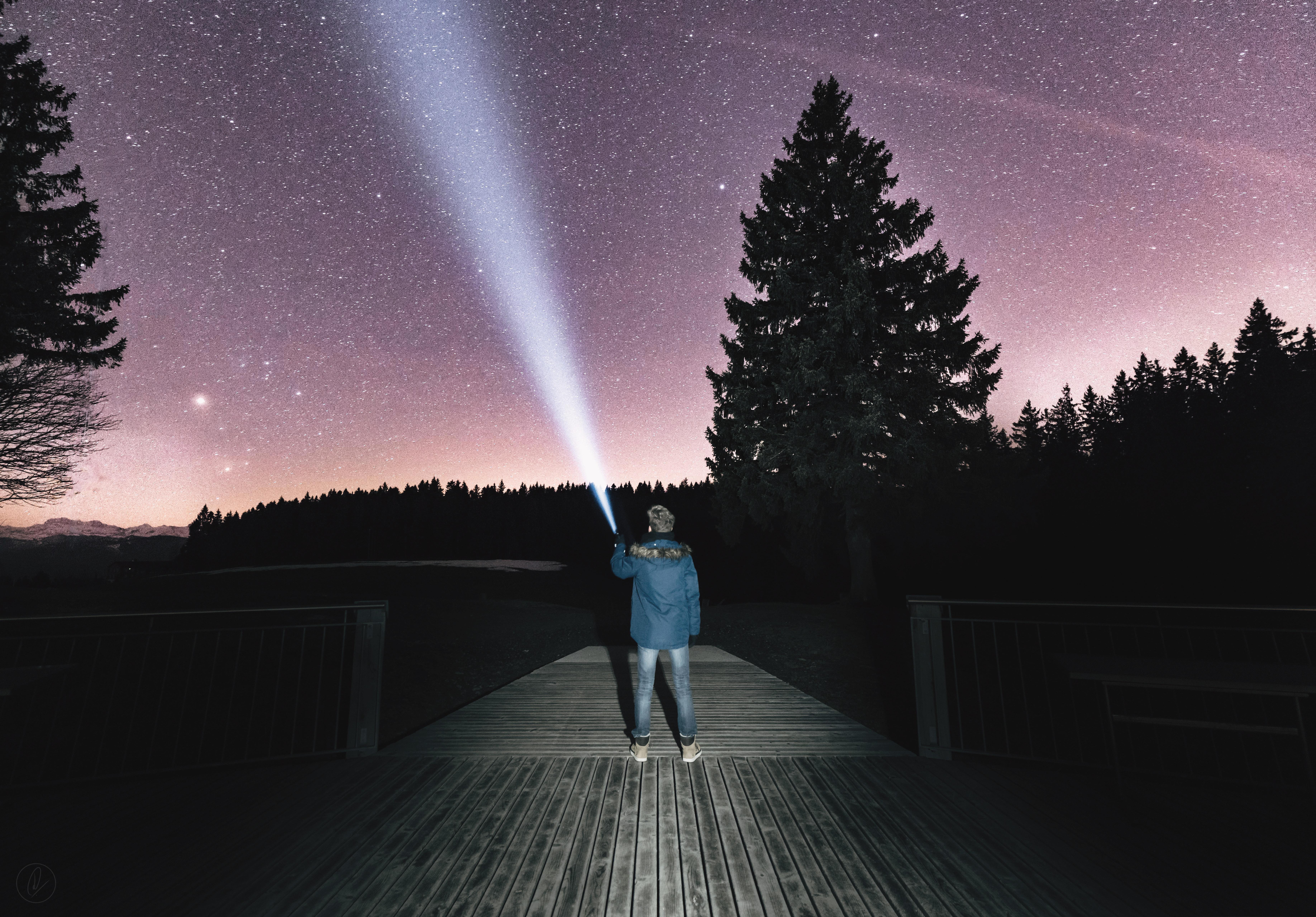 guy-holding-flashlight-to-the-purple-starry-night-sky