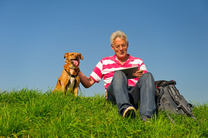 man-with-dog-sits-on-hill-while-reading-on-ipad