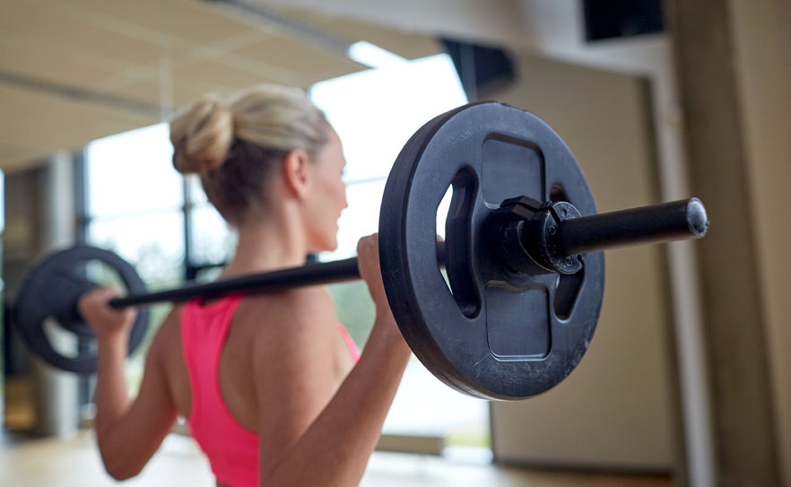 woman-lifts-barbell-behind-shoulders