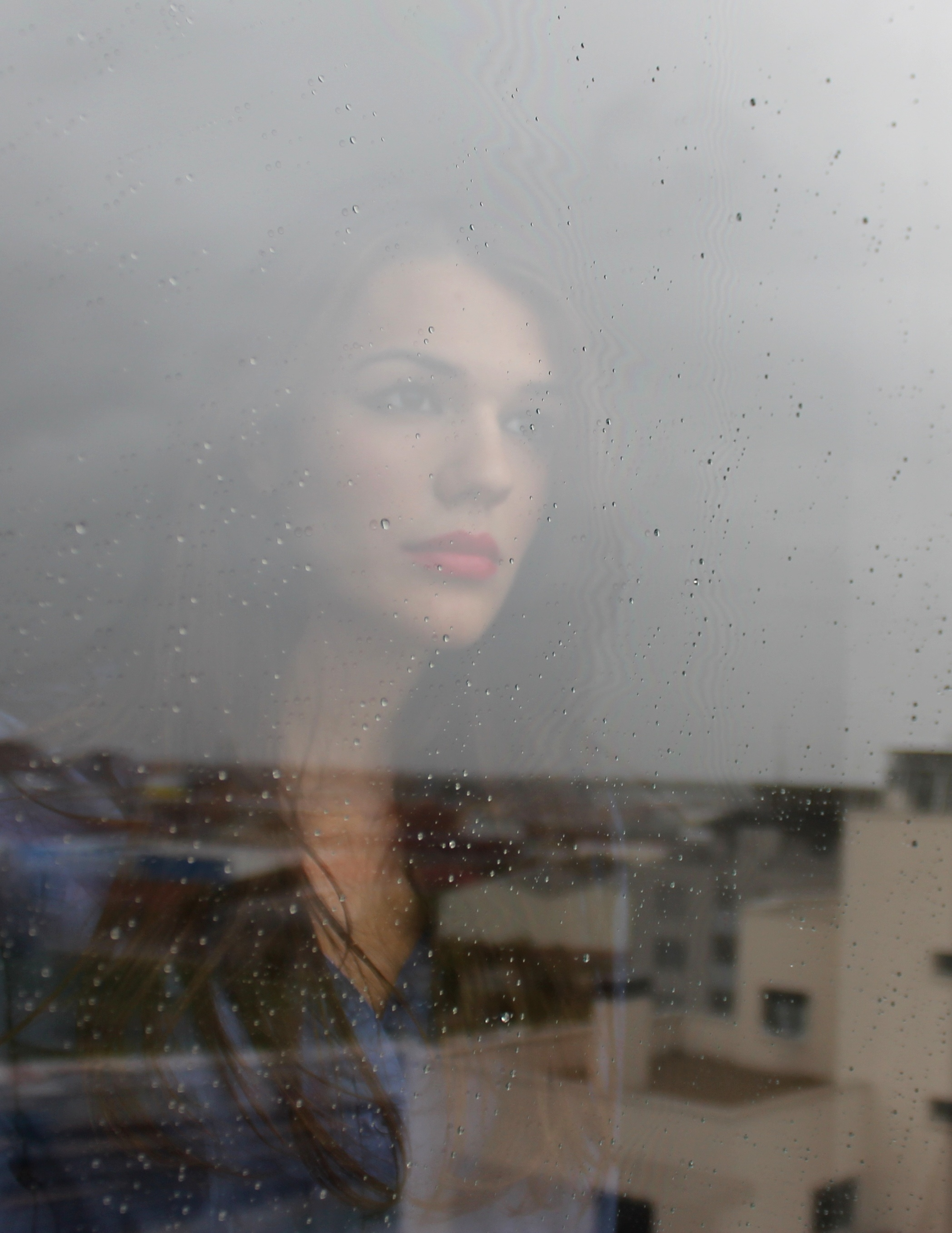 sad-woman-looking-out-the-window-in-the-rain