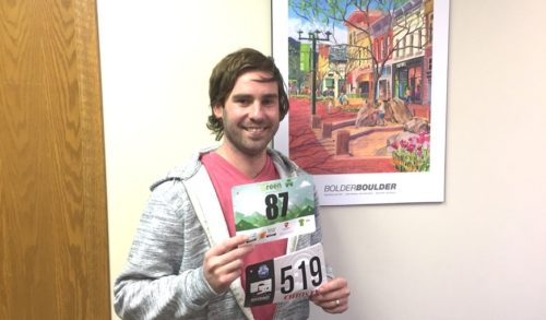 A man smiling and holding two race bibs in front of himself.