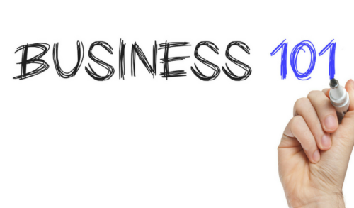 "A person's hand writing ""business 101"" in capital letters on a transparent surface"