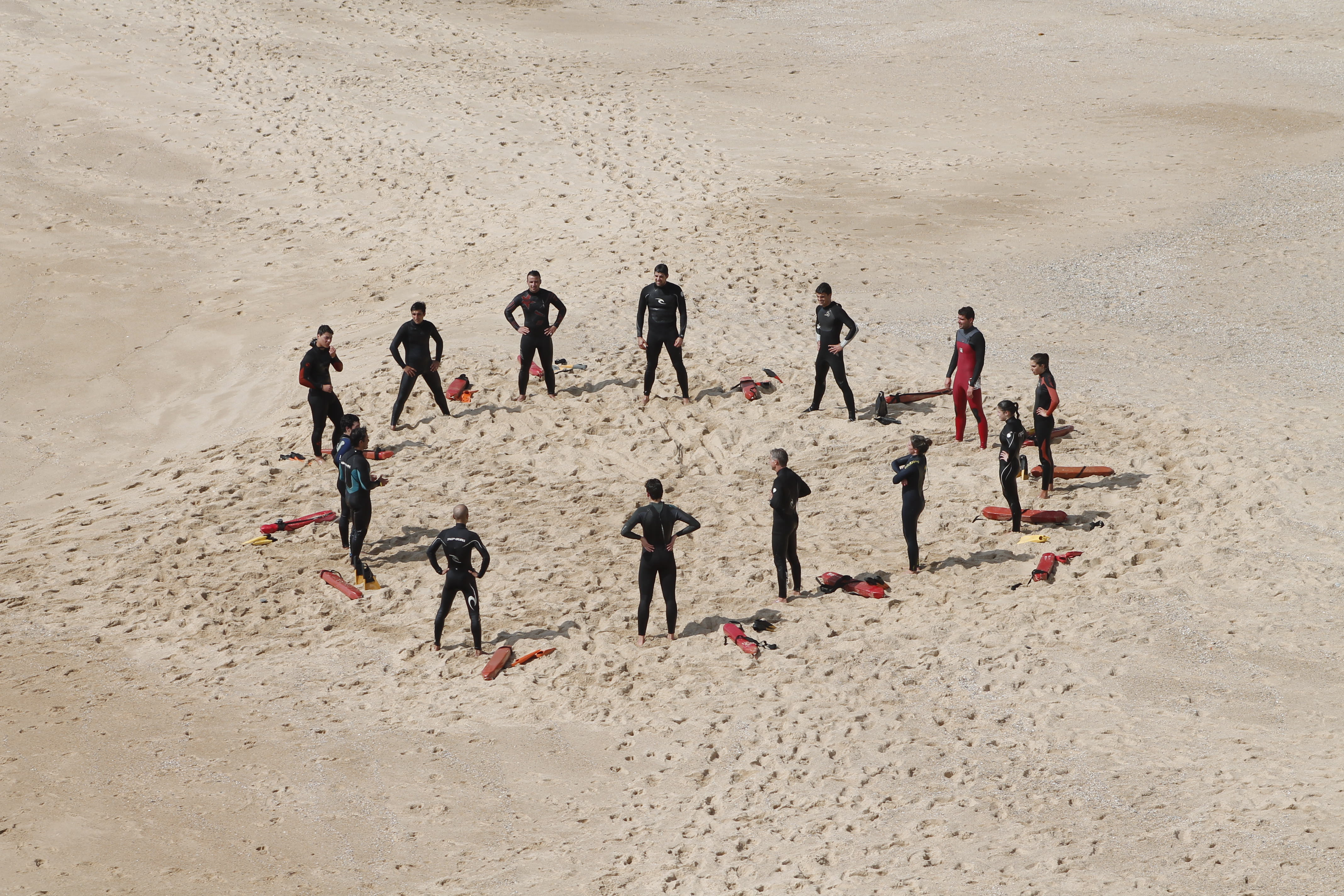 Lifeguards-in-wetsuits-learning-on-the-beach