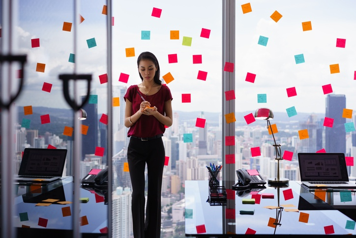 Busy-businesswoman-organizing-in-office-filled-with-sticky-notes