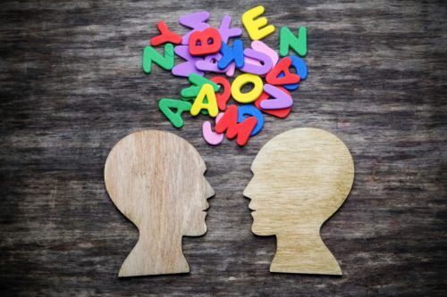 Silhouette cutouts of two people talking with colorful letters jumbled between them