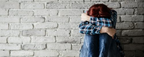 woman sitting against brick wall while hugging her knees with her head down