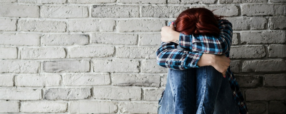 woman-sitting-against-brick-wall-hugging-her-knees-with-her-head-down