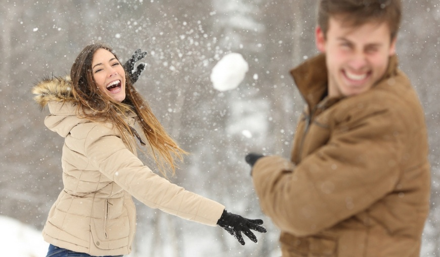Woman-playfully-throwing-snowball-at-guy