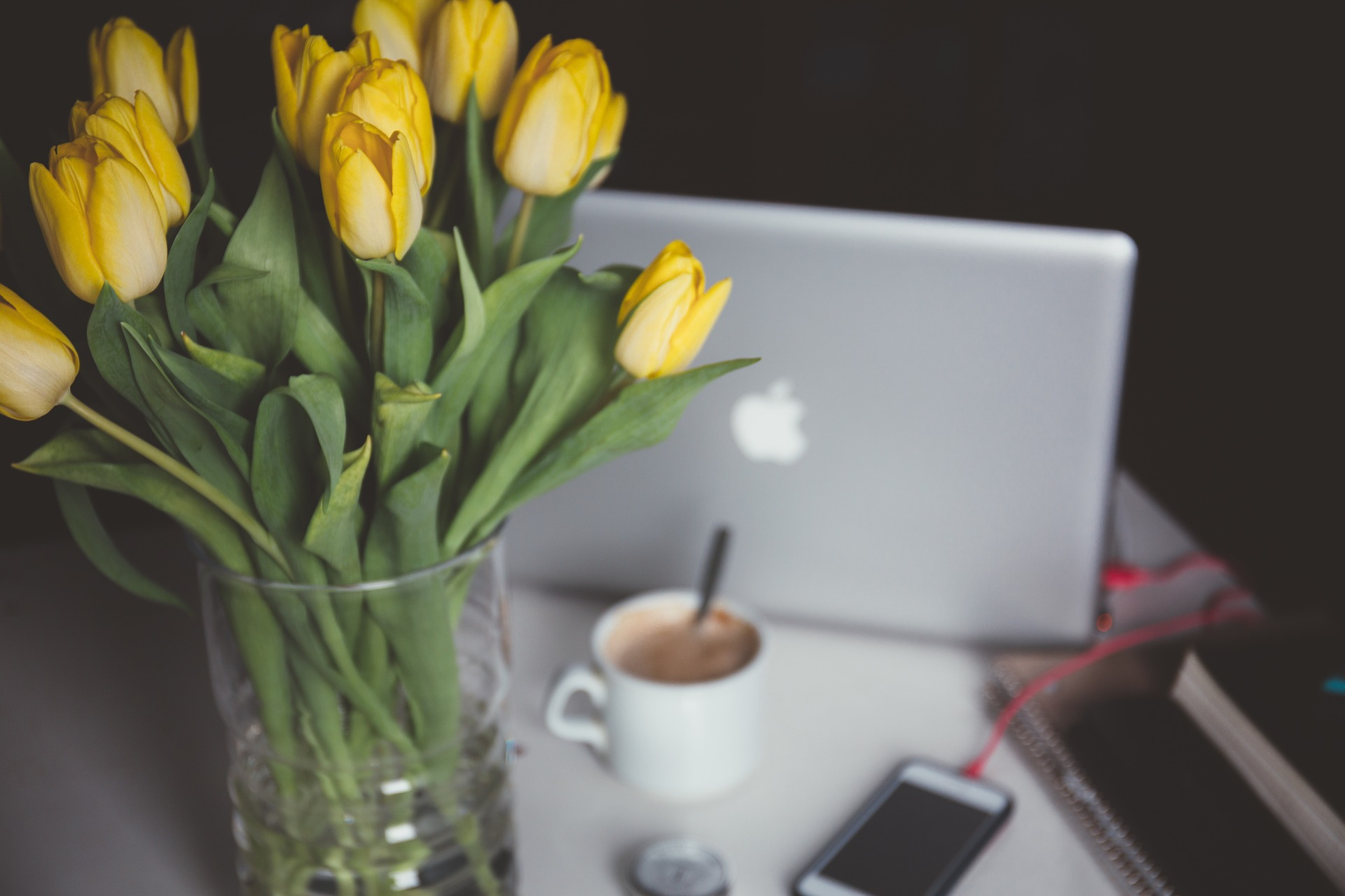 yellow-tulips-on-desk-with-coffee-laptop-and-smartphone