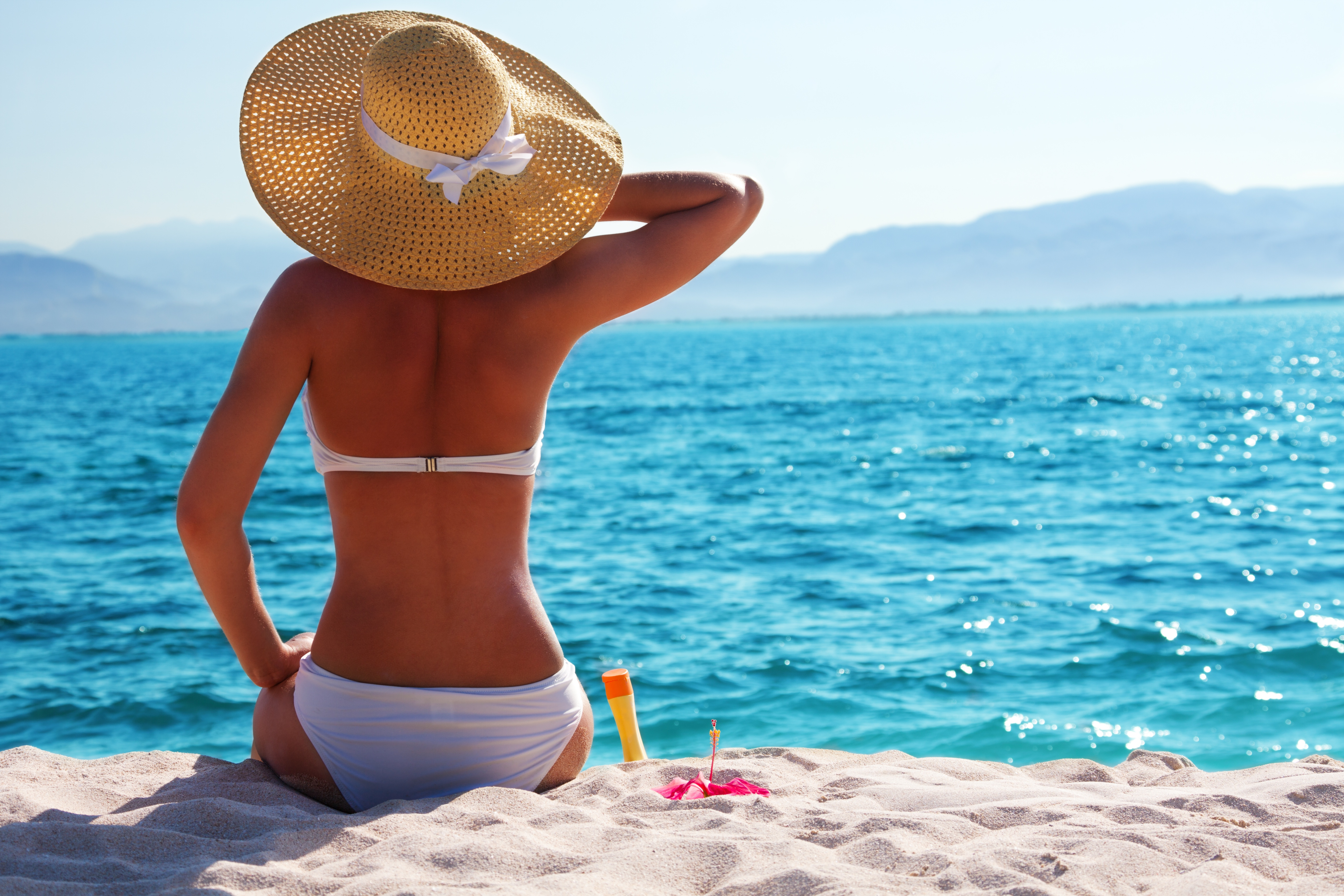 woman sitting on the beach wearing hat and bathing suit