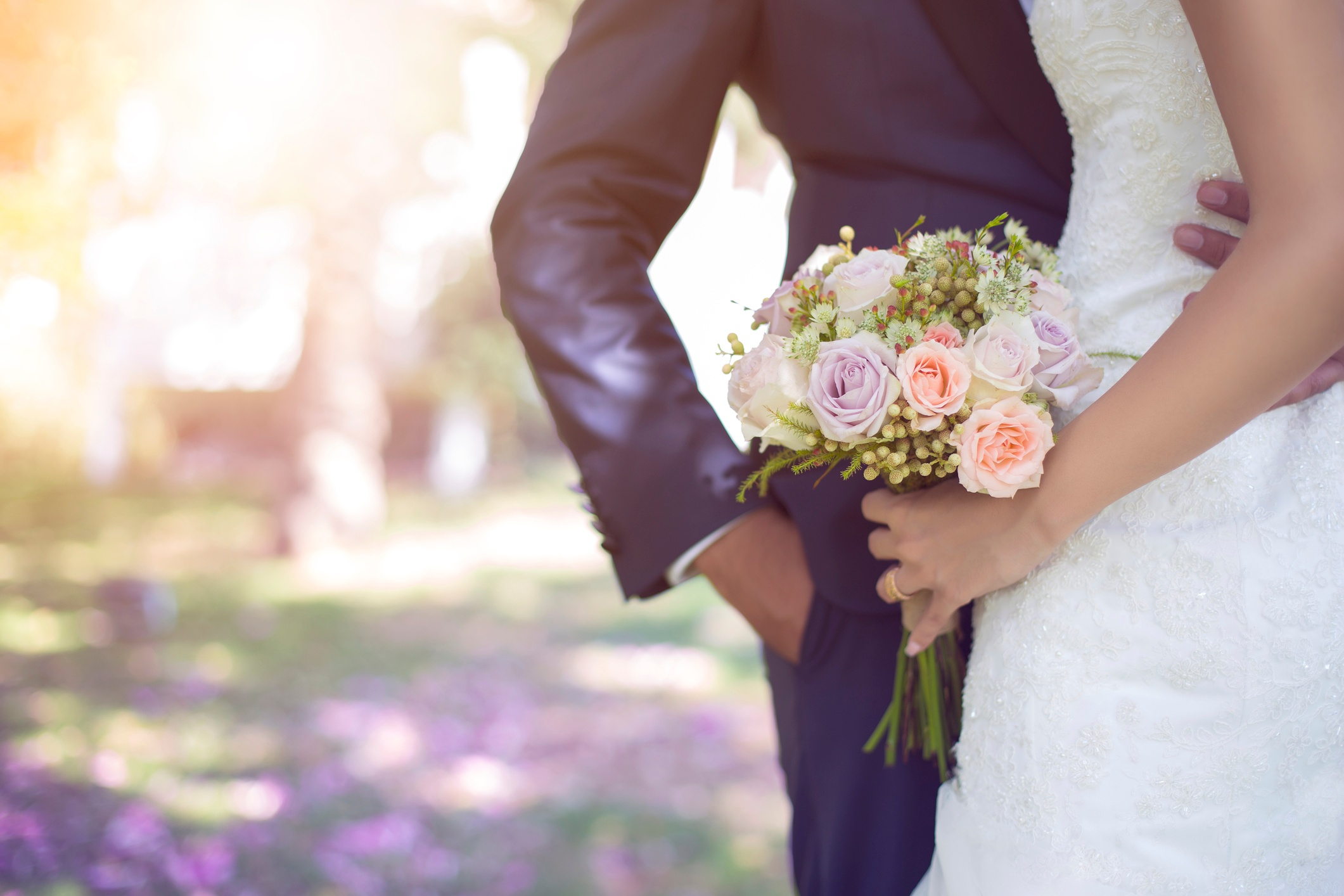 cropped-bride-and-groom-with-bouquet