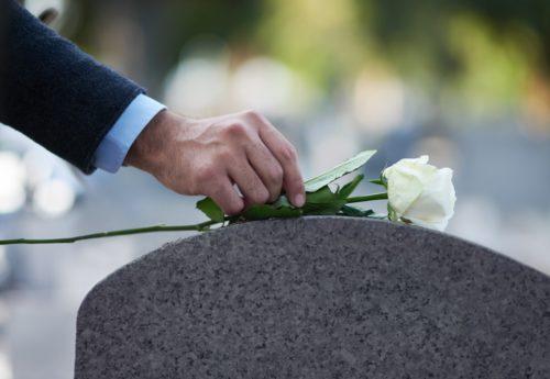 man-placing-white-flower-on-gravestone