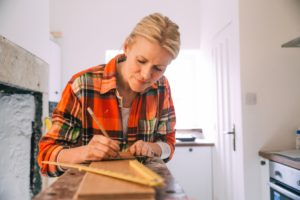 A woman wearing an orange flannel shirt works on a kitchen renovation project.