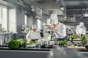 chef-plating-food-in-busy-restaurant-kitchen