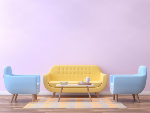 A pastel yellow couch and two light blue armchairs on a throw rug