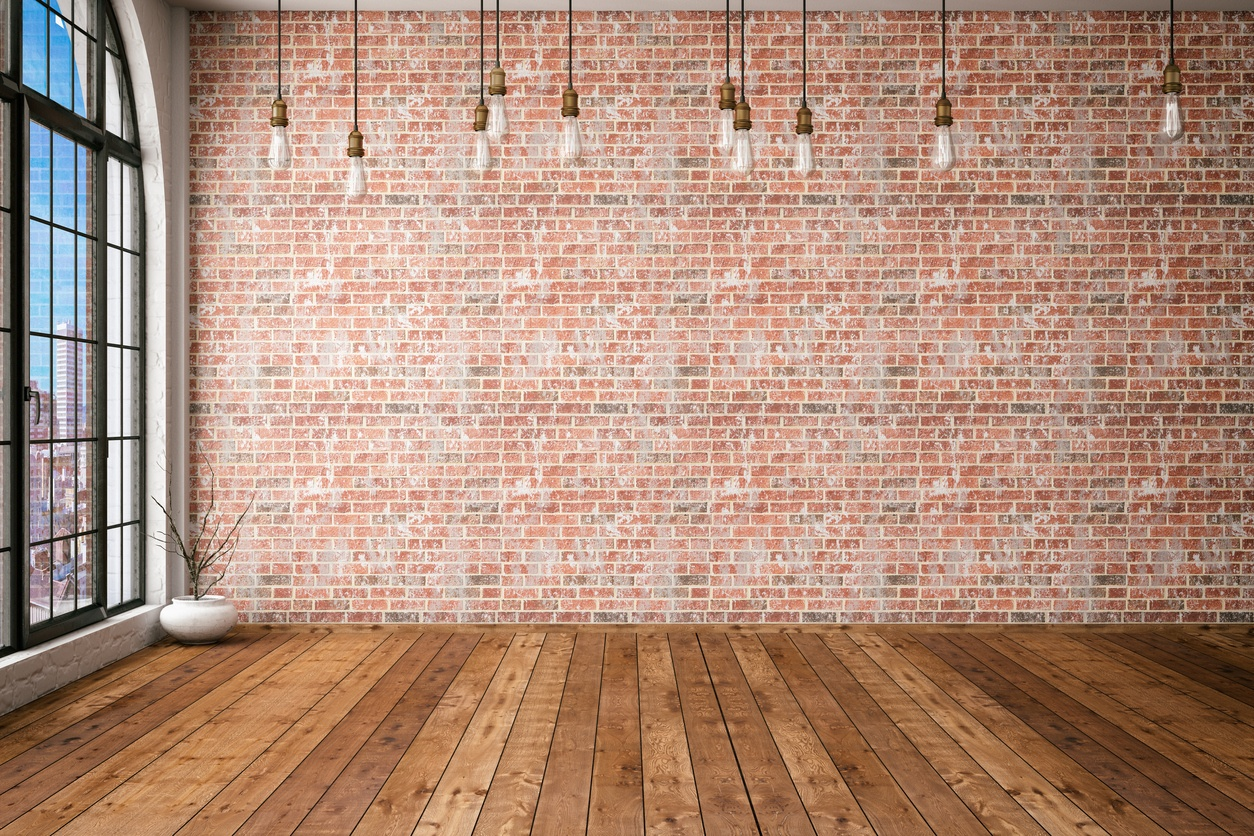 a-room-with-wood-flooring-brick-wall-and-several-bare-lightbulbs