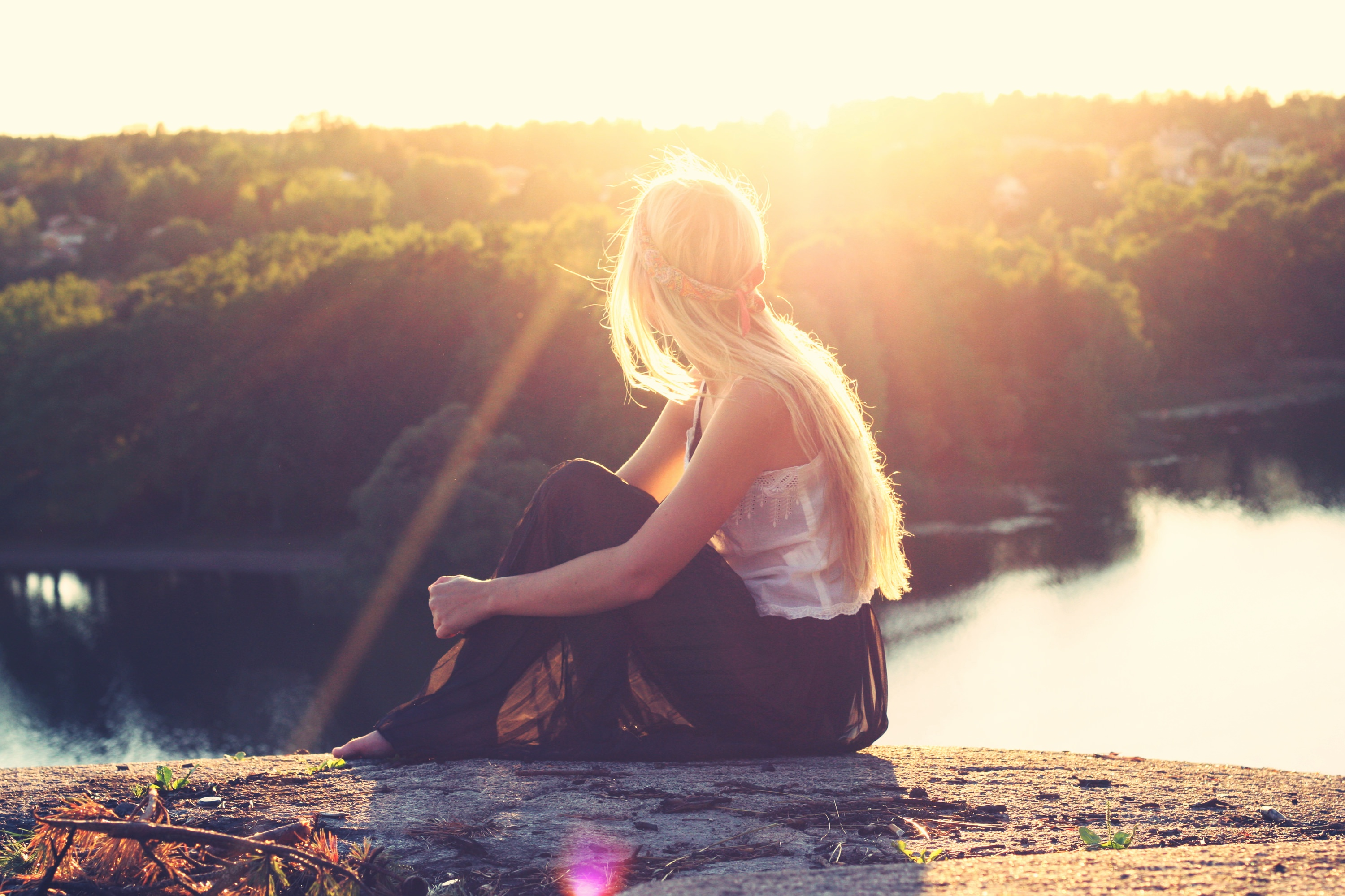 girl-with-long-blonde-hair-looking-out-over-lake-in-the-sunset