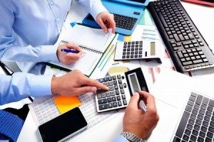 two-people-working-with-calculators-on-payroll