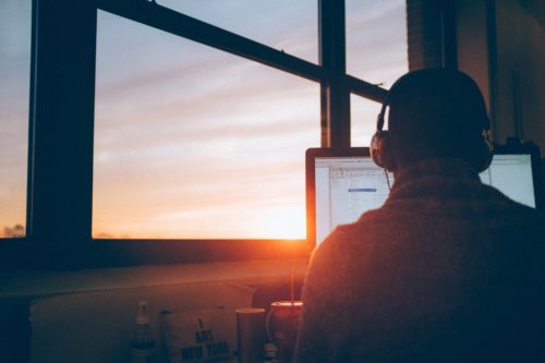 A person works on a computer while wearing headphones and sitting in front of a large window at sunset.