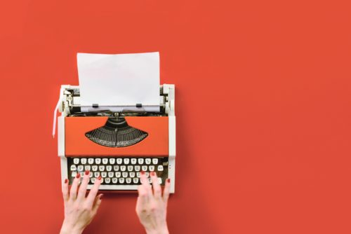 hands-typing-on-typewriter-orange-background