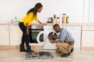 woman-watches-repair-technician-working-on-washing-machine-repair
