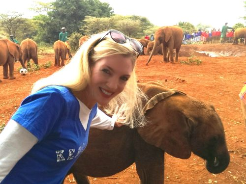 woman posing with baby elephant