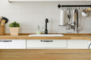 Wooden table with kitchen counter and sink background