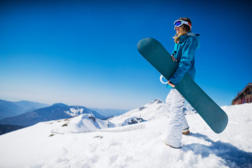 young woman stands on top of mountain holding a snowboard