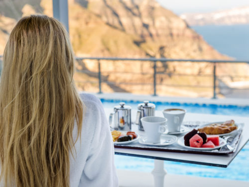 Horizontal color image of charming woman sitting at terrace and watching the beauty of nature in Santorini. Fresh breakfast in the morning.