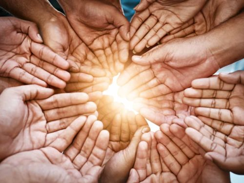 hands reaching out together in a circle to make the world brighter