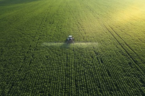 aerial shot tractor spreading herbicides over field