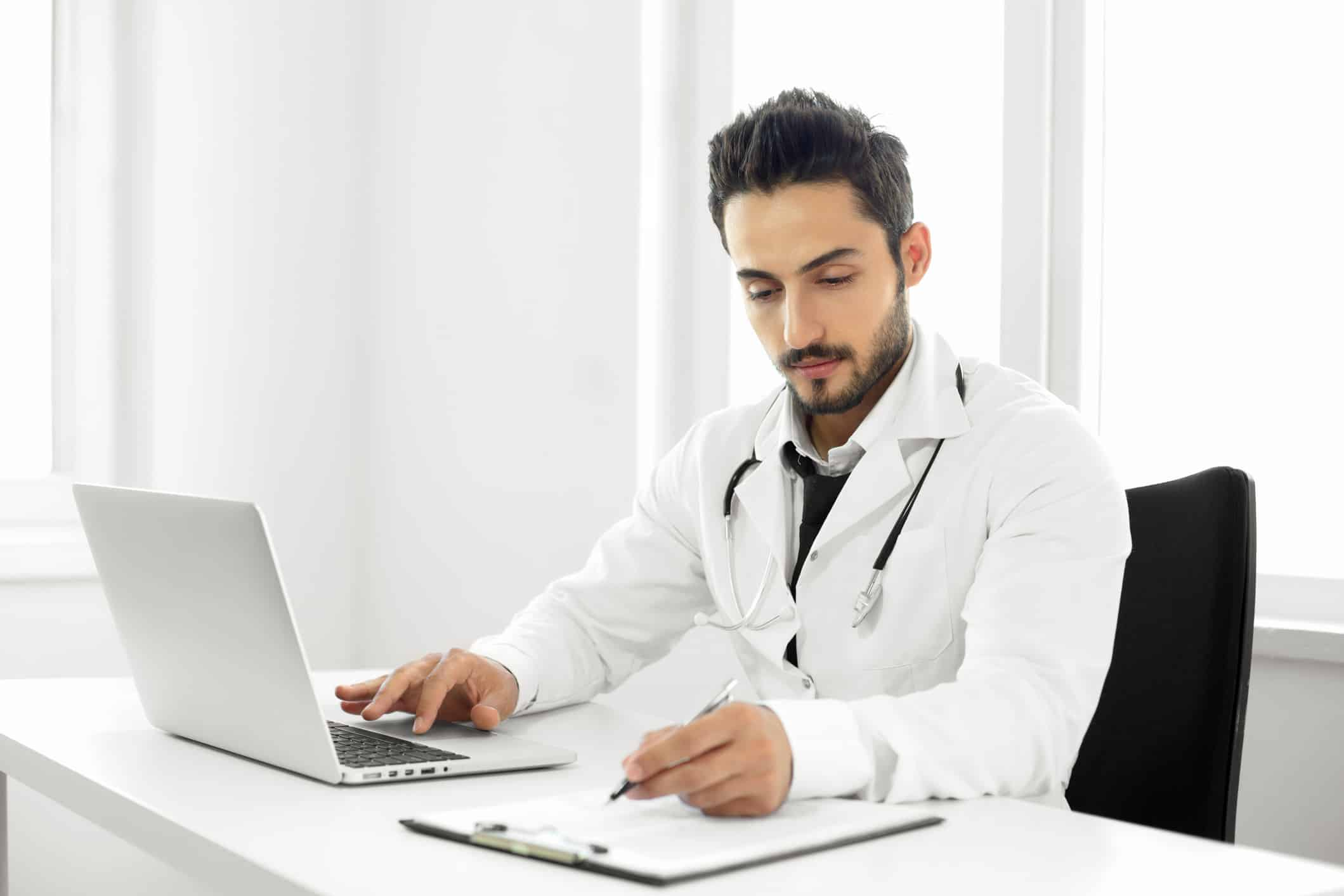 doctor writing and working on computer