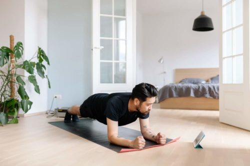 man doing beginner yoga at home with app